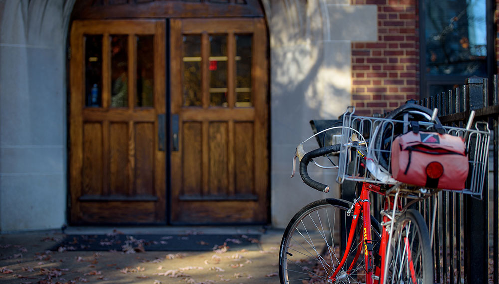 wooden door with bicycle parked in front on university campus